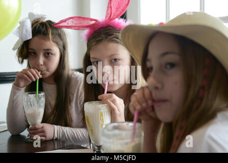 Three young children are sitting at a party table eating fried food and drinking milkshakes- there are balloons - Stock Photo