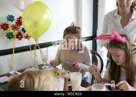 Four young children are sitting at a party table eating fried food and drinking milkshakes- there are balloons and - Stock Photo