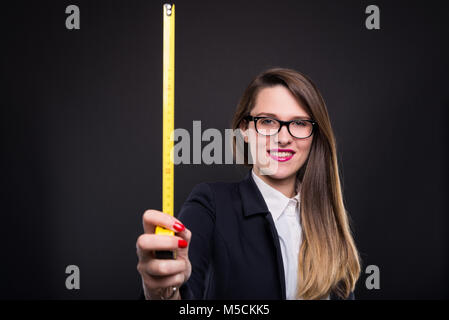 Young happy girl showing a yellow tape measure for renovation plan on dark background - Stock Photo