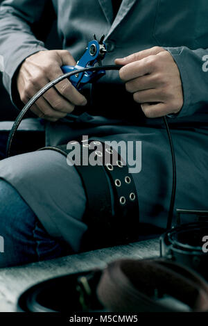 closeup of a young caucasian worker man, wearing a gray working coat, making a hole in a belt with a leather punch - Stock Photo
