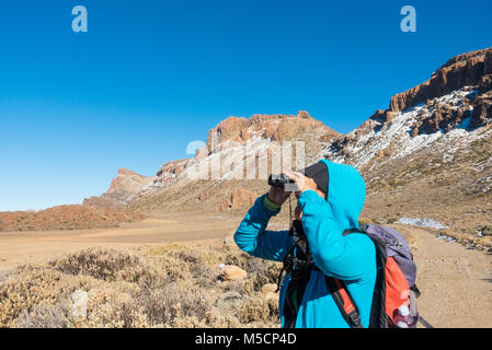 Female hiker on footpath in crater below mount Teide following recent snow. Parque Nacional del Teide, Tenerife, - Stock Photo