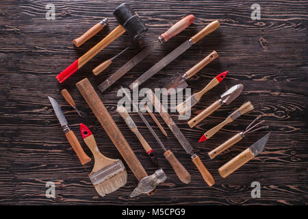 Assorted work tools on wooden black table. - Stock Photo