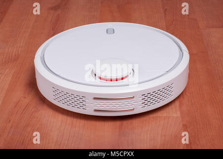 White robot vacuum cleaner on laminate floor cleaning dust in living room. Modern smart electronic housekeeping - Stock Photo