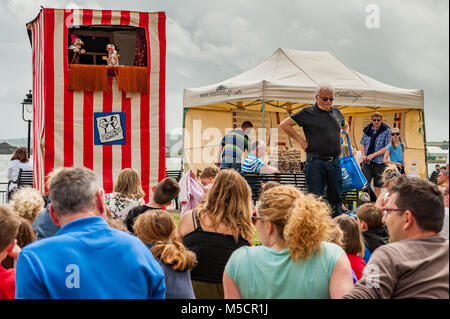 Traditional Punch and Judy show with people watching in Cobh Kennedy Park, Cobh, County Cork, Ireland. - Stock Photo