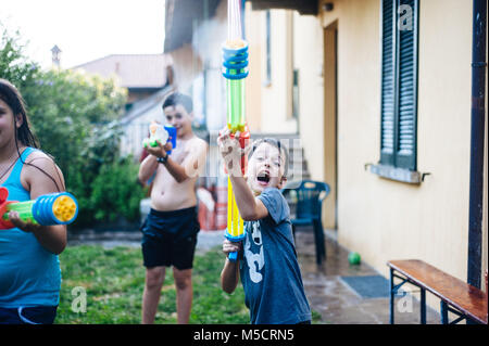 children play in the garden with guns and water rifles on a sunny summer day having a lot of fun - Stock Photo