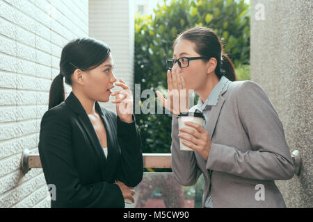 two beautiful Asian women talking about office gossip and feel shocked at rest time outdoor of the studio. - Stock Photo
