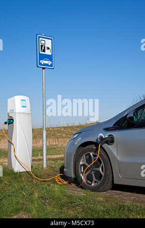 Power supply for electric car charging. Electric car charging station. Close up of the power supply plugged into - Stock Photo