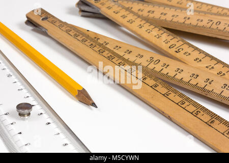A measuring stick, a ruler and a pencil on a white background - Stock Photo