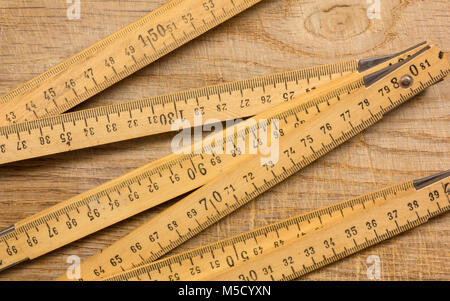 Measuring stick on an old wooden table - Stock Photo