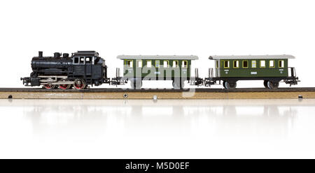 Vintage model electric train formed by a steam locomotive and two passenger cars on the rails - Stock Photo