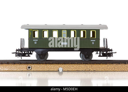 Green vintage passenger car of a model electric train on the rails - Stock Photo