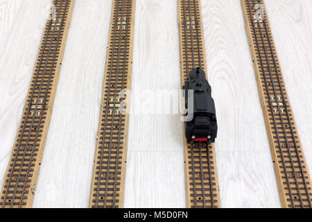 1950s vintage model steam locomotive on the rails over a wooden texture floor - Stock Photo
