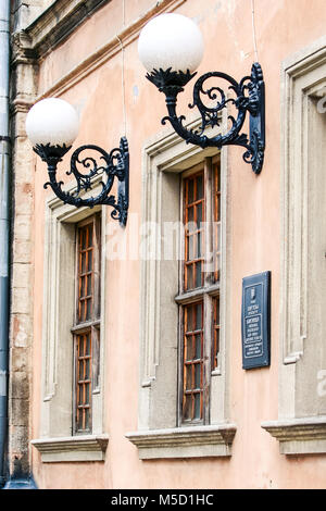 closeup age-old large brown wooden windows white round fantastic lanterns on pink wall of old building - Stock Photo