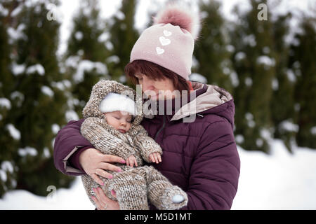 Grandmother holding little toddler boy outdoor on a snowy winter day, having their portrait taken - Stock Photo