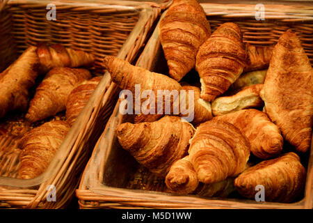 Puffy golden brown Croissants in sales wicker baskets, freshly baked, with natural lighting - Stock Photo