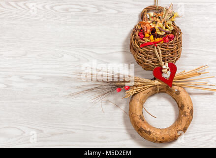 Small rustic ornamental wicker basket full of dried flowers and enriched with other decorations against a white - Stock Photo