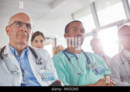 Attentive surgeons, doctors and nurses listening in meeting - Stock Photo