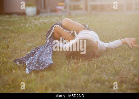 Serene girl laying in summer grass - Stock Photo