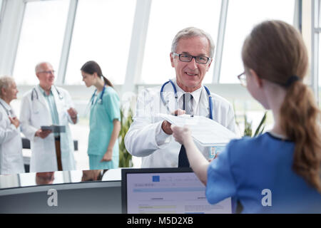 Male doctor handing clipboard to female nurse at hospital nurses station - Stock Photo