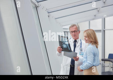 Male doctor showing x-ray to female patient in hospital - Stock Photo