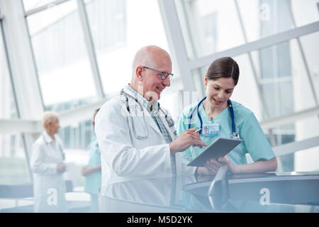 Doctor and nurse with digital tablet talking in hospital - Stock Photo