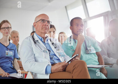 Attentive surgeons, doctors and nurses listening in conference - Stock Photo