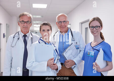 Portrait confident doctors and nurse in hospital corridor - Stock Photo