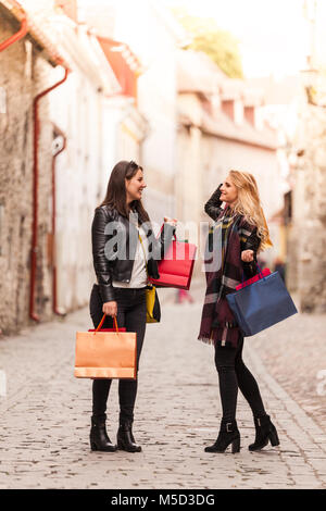 Woman and her friend walking on a street on a sunny day after going to a fair - Stock Photo