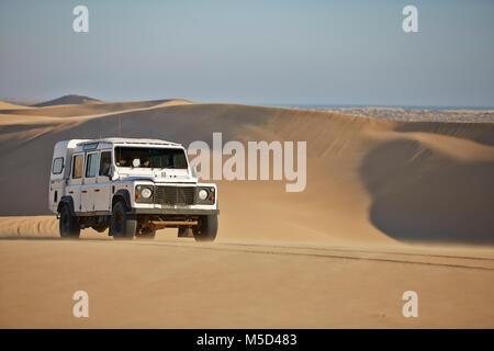 Off-road vehicle drives over sand dunes at Lange Wand on the Atlantic coast, Namib-Naukluft-Park, Namibia - Stock Photo