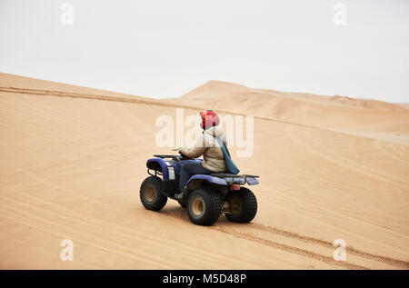 Woman drives with Quad over sand dunes at Swakopmund, Namibia - Stock Photo