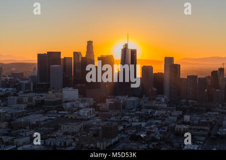 Dawn aerial view of rising sun behind downtown Los Angeles in Southern California. - Stock Photo