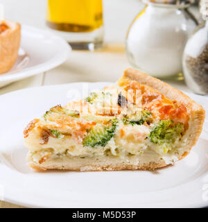 Classic salmon and broccoli quiche made from shortcrust pastry with broccoli florets and smoked salmon in a creamy - Stock Photo