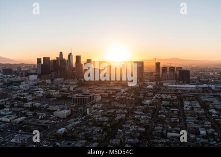 Los Angeles, California, USA - February 20, 2018:  Aerial view of morning sunrise behind urban buildings in downtown - Stock Photo
