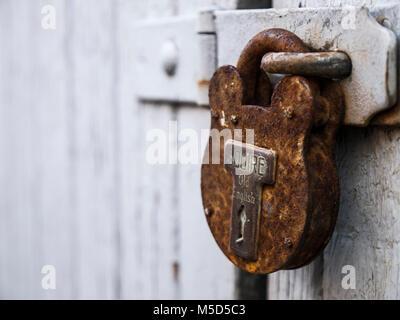 Rusty padlock on old garage door - Stock Photo