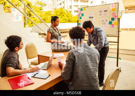 Business and Teamwork Concept: Businessmen and woman brainstorming in corporate planning conference meeting with - Stock Photo