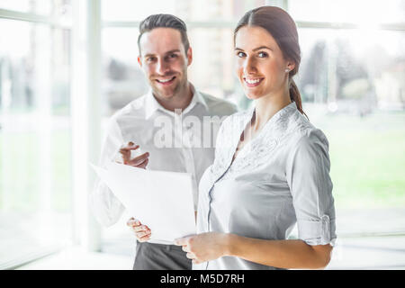 Portrait of happy young businesspeople discussing over documents in office - Stock Photo