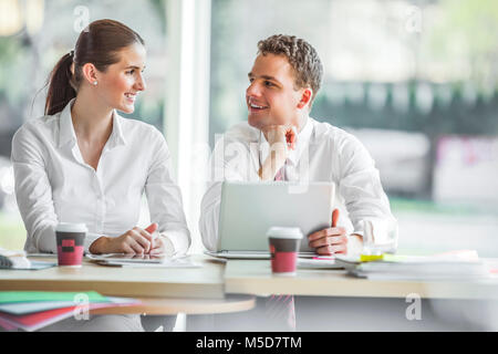 Smiling young businesspeople discussing at office desk - Stock Photo