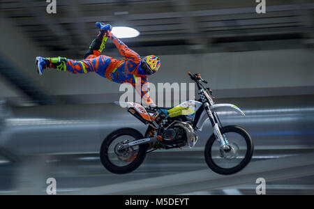 22 February 2018, Germany, Hamburg: A stunt driver shows tricks on his motorbike at the 'Hamburg Motor Days' fair - Stock Photo