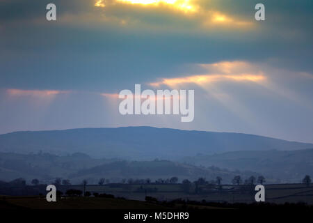A dramactic lanscape in Wales at sunset as Crepuscular rays break through the clouds to light the rural landscape - Stock Photo