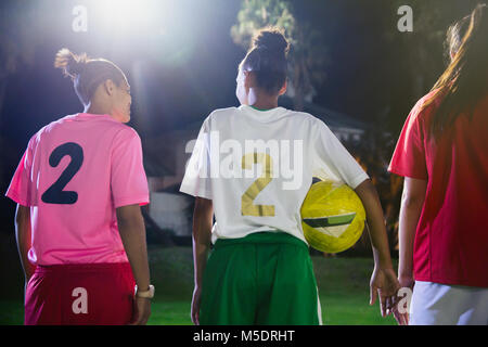 Young female soccer players with ball talking on field at night - Stock Photo
