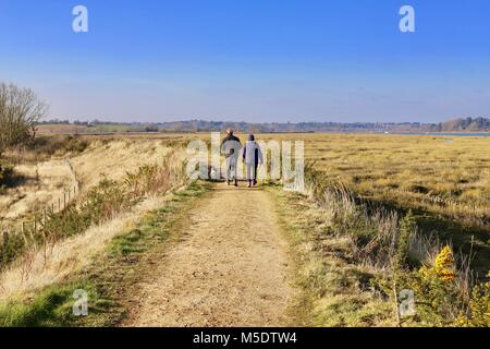 A couple of adults enjoying a countryside walk in rural Suffolk. On the river wall by the River Deben, Waldringfield, - Stock Photo