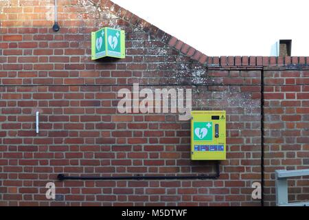 Defibrillator / emergency life saving equipment with code lock wall mounted for public use. Outside The Maybush - Stock Photo