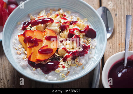 Strawberry porridge with oats, mashed banana and plum and blueberry sauce - Stock Photo