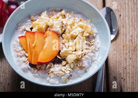 Strawberry porridge with oats, mashed banana and plum - Stock Photo