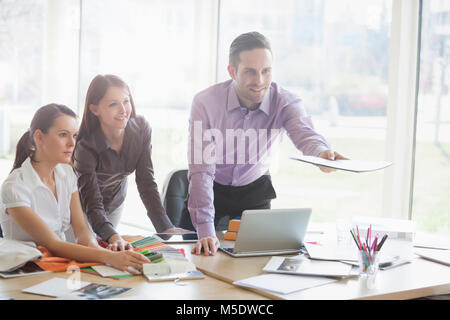 Young business people working at desk in creative office - Stock Photo