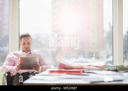 Young businessman using digital tablet at conference table in creative office - Stock Photo
