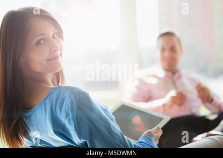 Portrait of beautiful young businesswoman holding digital tablet with male colleague in background at office - Stock Photo