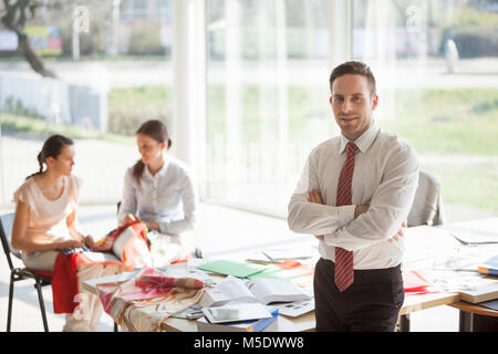 Portrait of confident young businessman with female colleagues in background at creative office - Stock Photo