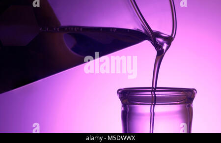 Beaker Pouring Into Flask In Lab - Stock Photo