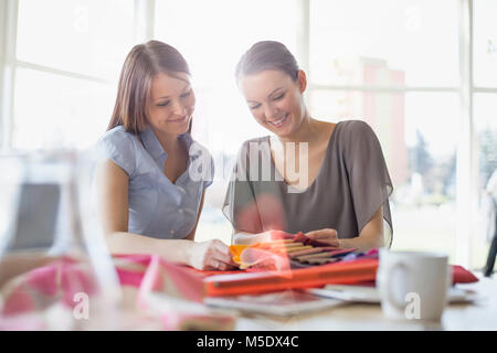 Young businesswomen discussing over fabric swatches in office - Stock Photo